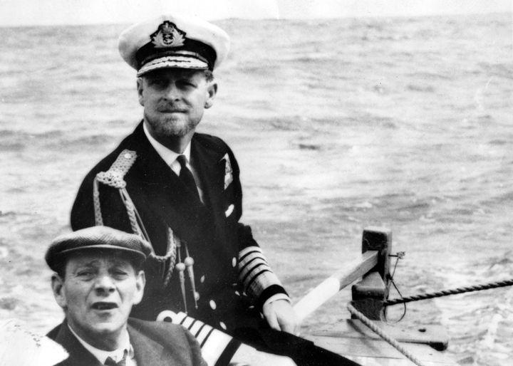 """Le prince Philip, barbu et en uniforme, le 7 février 1957, à la barre du """"Lorna"""" après être descendu du """"Britannia"""" au large de l'île britannique de Tristan da Cunha dans l'Atlantique Sud. (KEYSTONE PICTURES USA / MAXPPP)"""