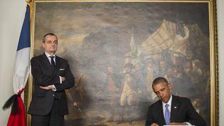 """Le président américain, Barack Obama, signe un cahier de condoléances pour les victimes de l'attentat contre """"Charlie Hebdo"""", aux côtés de Gérard Araud, ambassadeur de France, le 8 janvier 2015, à Washington (Etats-Unis). (JIM WATSON / AFP)"""