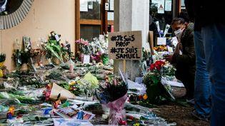 Au lendemain de l'assassinat de l'enseignant Samuel Paty, de nombreuses personnes lui ont rendu hommage, le 17 octobre 2020, devant le collège du Bois d'Aulne, à Conflans-Sainte-Honorine (Yvelines), où il enseignait. (MARIE MAGNIN / HANS LUCAS / AFP)