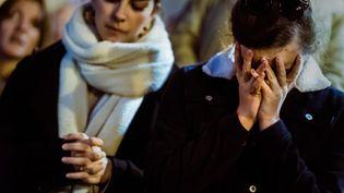 Des badauds prient devant l'incendie qui a ravagé Notre-Dame de Paris, le 15 avril 2019. (SIMON GUILLEMIN / HANS LUCAS / AFP)