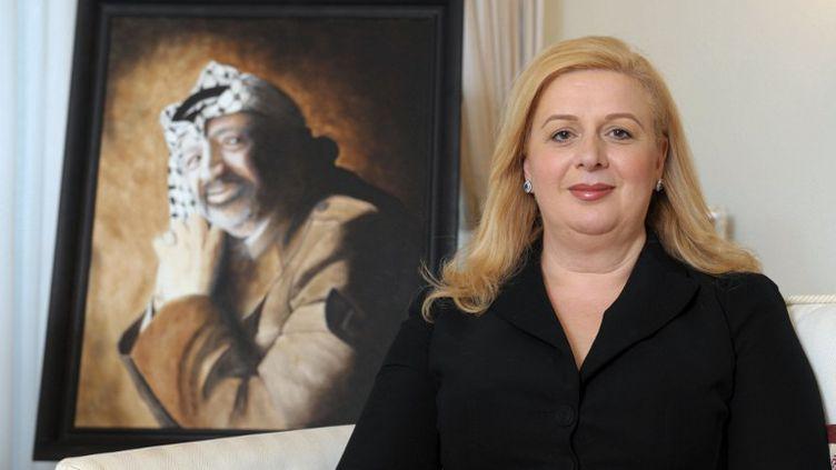Souha Arafat pose devant le portrait de Yasser Arafat, en novembre 2011, à Malte. (MATTHEW MIRABELLI / AFP)