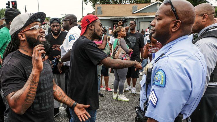 Rassemblés pour manifester contre les violences policières à la suite de la mort d'un adolescent noir, des habitants de Saint Louis font face aux forces de l'ordre, mercredi 19 août 2015. (LAWRENCE BRYANT / REUTERS)