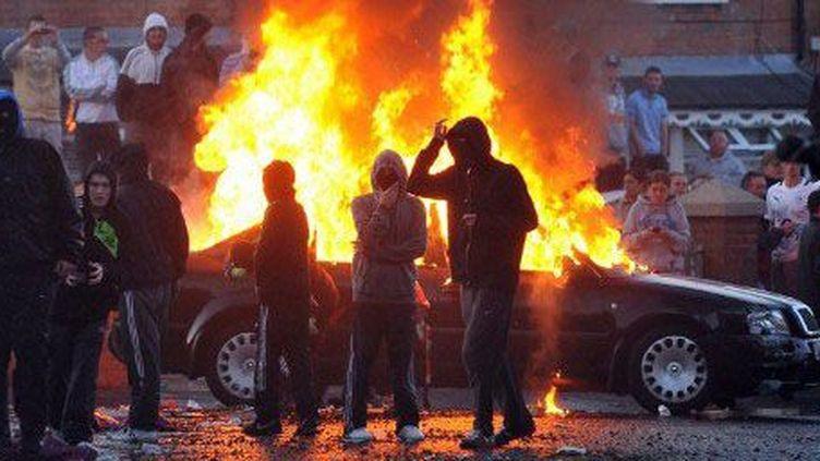 Jeunes protestants jetant des pierres et des cocktails Molotov sur la police pendant une émeute à Belfast le 12 juillet 2012. (AFP - Stephen Wilson)