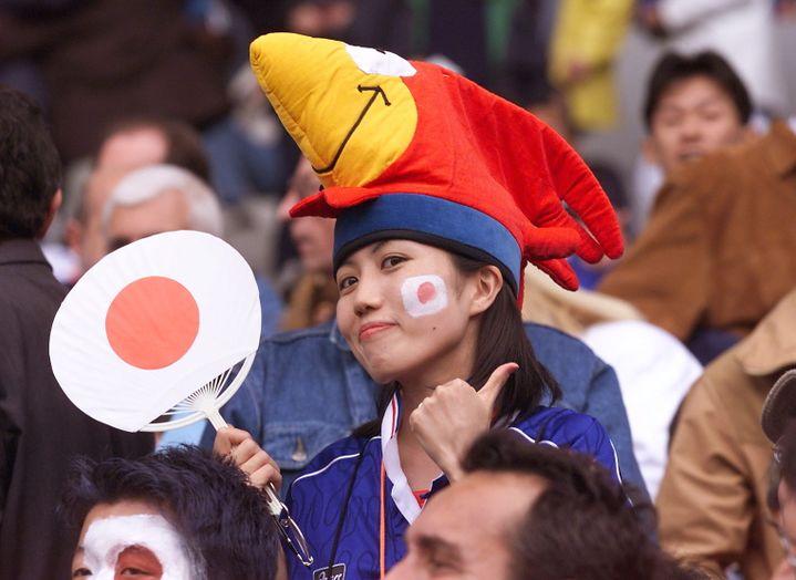 Une supportrice japonaise porte un chapeau à l'effigie de Footix, lors du match Argentine-Japon, le 14 juin 1998 à Toulouse (Haute-Garonne). (JACQUES DEMARTHON / AFP)