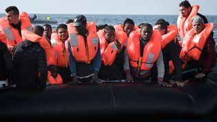"""Des migrants équipés de gilets de sauvetage transférés sur """"l'Aquarius"""", aux abords des côtes lybiennes, le 12 mai 2018. (LOUISA GOULIAMAKI / AFP)"""