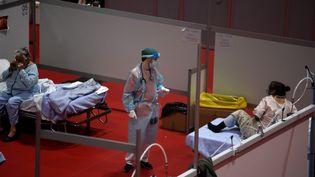 Un soignant et des patientes d'un hôpital temporaire pour les malades du Covid-19 installé dans un palais des congrès à Madrid (Espagne), le 13 avril 2020. (JUAN CARLOS LUCAS / NURPHOTO / AFP)