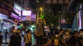 Un manifestant avec un masque à gaz pointe un laser, signe de protestation contre les violences policières, devant le commissariat de Shum Shui Po, à Hong Kong (Chine), le 14 août 2019. (VERNON YUEN / NURPHOTO / AFP)