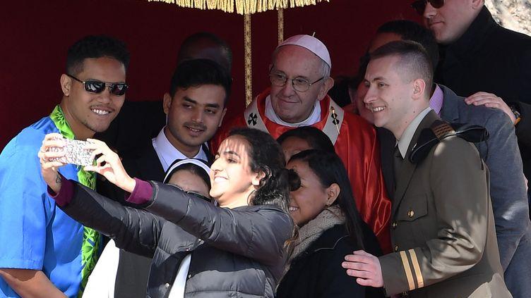 Le pape François prend la pose pour un selfie avec des jeunes fidèles, dimanche 25 mars 2018 sur la place Saint-Pierre au Vatican. (TIZIANA FABI / AFP)