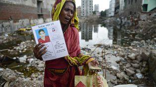 Une proche d'une des victimes du Rana Plaza, le 24 avril 2013, devant les décombres de l'immeuble à Dacca (Bangladesh). (MUNIR UZ ZAMAN / AFP)
