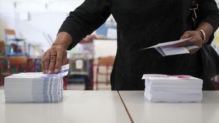 Une femme vote à Saint-Denis, sur l'île de la Réunion, pour le second tour des élections législatives, le 18 juin 2017. (RICHARD BOUHET / AFP)