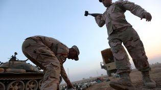 Des combattants irakiens engagés dans la bataille de Mossoul, et un lot d'obus de mortiers confisqué aux jihadistes de l'Etat islamique, le 7novembre. (SAFIN HAMED / AFP)