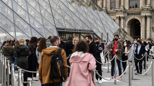 Des visiteurs attendent devant le musée du Louvre, le 19 mai 2021. (ALAIN JOCARD / AFP)