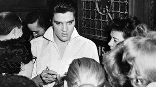 Elvis Presley est entouré de fans, en 1958, en Californie. (AFP)