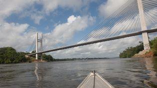 Une pirogue navigue sur le fleuve Oyapock, frontière naturelle entre la Guyane et le Brésil, le 27 juillet 2012 près de Saint Georges de l'Oyapock. Manoelzinho, chef d'une bande suspectée par les autorités d'avoir tué deux militaires français, a été arrêté le 27 juillet sur la rive de l'Amazone. (JEROME VALLETTE / AFP)