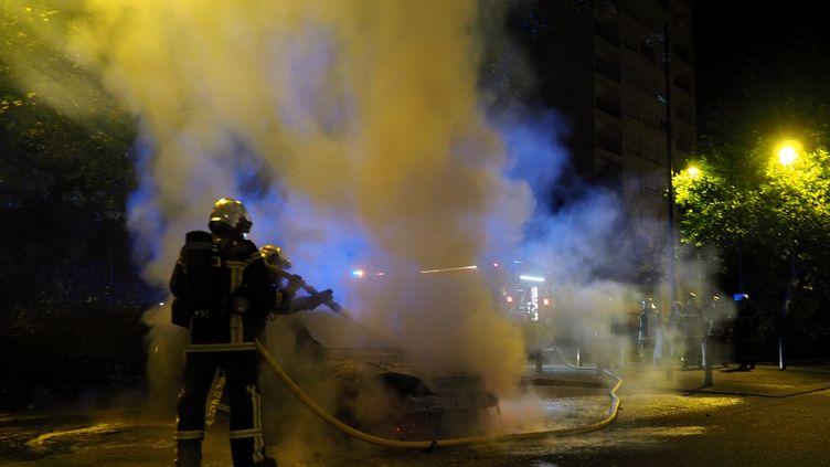 Des pompiers interviennent sur un incendie de véhicule, quartierLe Breil, à Nantes, dans la nuit du 7 au 8 juillet. (GUILLAUME SOUVANT / AFP)