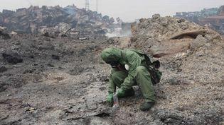 Un soldat fouille les décombres de l'entrepôt qui a explosé à Tianjin (Chine), le 15 août 2015. (WANG HAOBO / XINHUA / AFP)