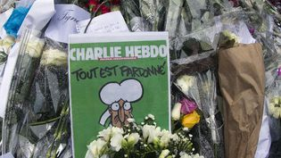 Le Une du Charlie Hebdo du 14 janvier 2015 au milieu des fleurs déposées devant le siège de l'hebdomadaire  (JOEL SAGET / AFP)