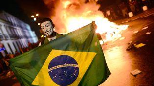 Un manifestant déploie un drapeau brésilien, lors d'affrontements avec les forces de l'ordre, à Rio de Janeiro, le 17 juin. (CHRISTOPHE SIMON / AFP)