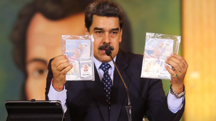 Le président vénézuélien Nicolas Maduro brandit les passeports et les cartes professionnelles de deux Américains arrêtés, le 6 mai 2020, à Caracas. (MARCELO GARCIA / VENEZUELAN PRESIDENCY / AFP)