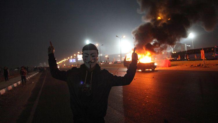 Un Egyptien portant le masque du mouvement Anonymous pose devant une voiture en flammes, à l'entrée du stade du Caire (Egypte), le 8 février 2015. (AFP)