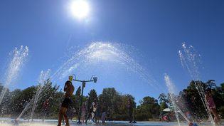 Des enfants se rafraîchissent sous des jets d'eau, pendant un été de fortes chaleurs, le 1er août 2013 à Strasbourg (Bas-Rhin). (PATRICK HERTZOG / AFP)