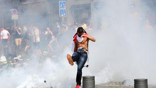 Un supporter anglais frappe dans une grenade lacrymogène à Marseille (Bouches-du-Rhône), le 11 juin 2016. (LEON NEAL / AFP)