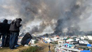 """Des réfugiés regardent la fumée qui s'élève au-dessus des abris de fortune en feu dansla """"Jungle"""" à Calais, le 26 octobre 2016, lors du démantèlement du camp. (PHILIPPE HUGUEN / AFP)"""