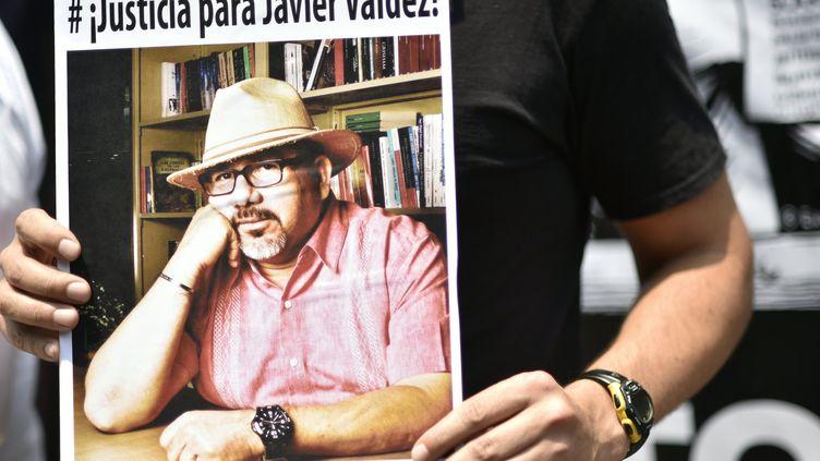 Un homme tient une photo du journaliste mexicain assassiné Javier Valdez lors d'une manifestation en sa mémoire à Mexico, le 16 mai 2017. (PEDRO PARDO / AFP)