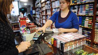 Une femme achète des cartouches de cigarettes, le 30 septembre 2012, à Les (Espagne), à la frontière avec la France. (REMY GABALDA / AFP)