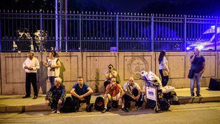 Des passagers attendent à l'extérieur de l'aéroport international Atatürk, à Istanbul (Turquie), le 28 juin 2016. (OZAN KOSE / AFP)