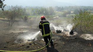 Un pompier du Varéteint les restes de végétation fumante dans le massif des Maures, le 17 août 2021. (NICOLAS TUCAT / AFP)