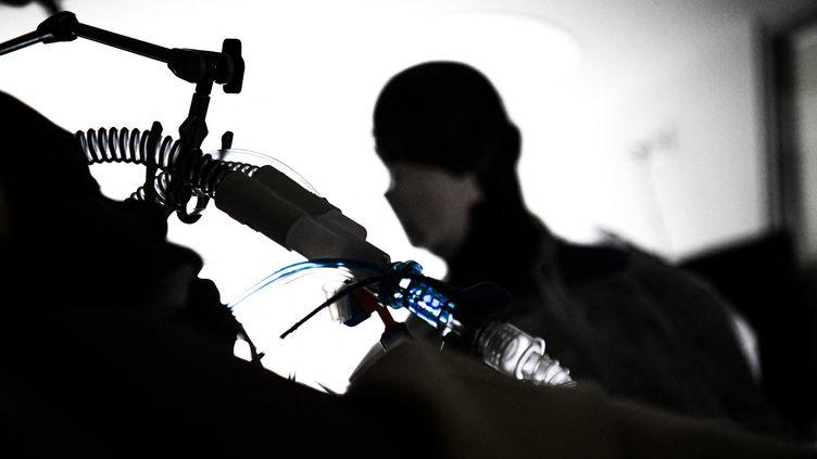Un soignant s'occupe d'un patientinfectés par le Covid-19dans un service de réanimation à l'hôpital Ambroise Pare de l'AP-HP à Boulogne-Billancourt, le 8 mars 2021. Photo d'illustration. (ALAIN JOCARD / AFP)