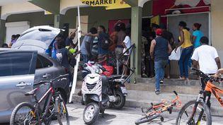 Des personnes se servent dans une boutique sur l'île deSaint-Martin après le passage de l'ouragan Irma, jeudi 7 septembre 2017. (LIONEL CHAMOISEAU / AFP)