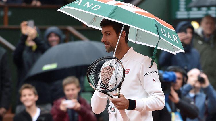 Le Serbe Novak Djokovic s'amuse de la pluie qui tombe sur Roland-Garros le 31 mai 2016 à Paris. (ERIC FEFERBERG / AFP)