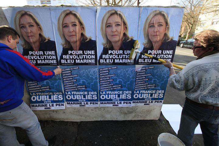 Des militants FN collent des affiches à l'effigie de Marine Le Pen, le 20 février 2012 à Hénin-Beaumont. (PASCAL ROSSIGNOL / REUTERS)