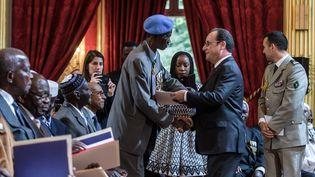 François Hollande salue un vétéran durant une cérémonie de naturalisation d'anciens tirailleurs sénagalais, à l'Elysée, le 15 avril 2017. (CHRISTOPHE PETIT TESSON / AFP)