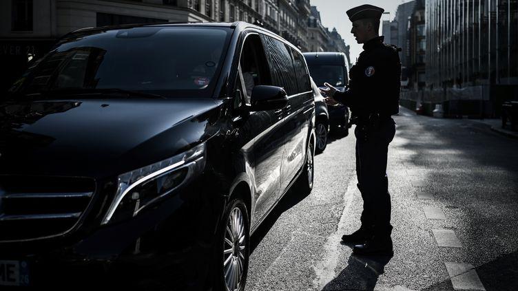 Un policier contrôle un automobiliste à Paris, le 19 mars 2020, au troisième jour du confinement imposé par l'Etat pour combattre l'épidémie de Covid-19. (PHILIPPE LOPEZ / AFP)