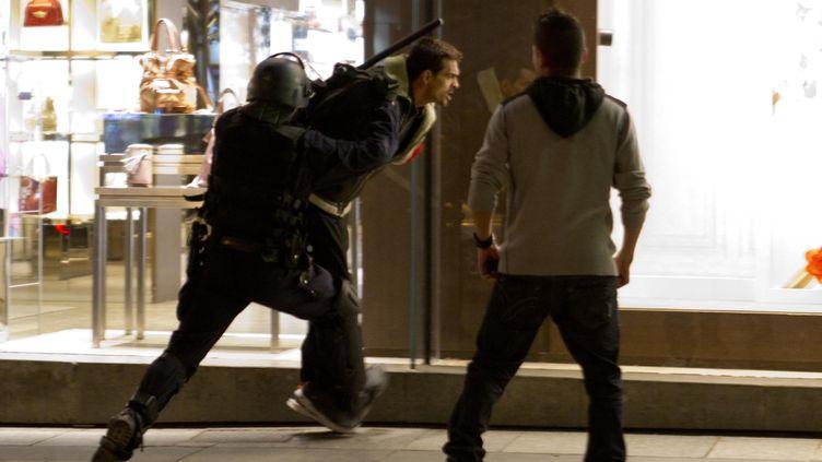 Un homme est arrêté par un policier en tenue, le 13 mai 2013, à Paris, après les célébrations du titre du PSG. (VINCENT WARTNER / 20 MINUTES / SIPA)