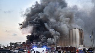 Un hélicoptère tente d'éteindre l'incendieaprès une explosion au port de Beyrouth au Liban, le 4 août 2020. (STR / AFP)