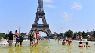 Des gens se rafraîchissent dans des bassins à proximité de la tour Eiffel, à Paris, lors d'un épisode de canicule, le 1er juillet 2015. (MUSTAFA YALCIN / ANADOLU AGENCY / AFP)