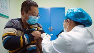 Un membre du personnel d'un aéroport reçoit une injection du vaccin contre le Covid-19 au centre de santé de Dizhang, dans la province du Shaanxi, au nord-ouest de la Chine, le 25décembre 2020. (WEI XIANG / XINHUA / AFP)