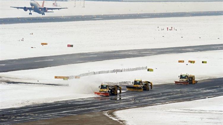 Ballet de chasse-neige à l'aéroport de Heathrow en Grande-Bretagne, submergée par la neige... (AFP - Carl de Souza)