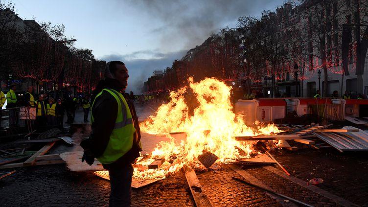 """Des """"gilets jaunes"""" devant une barricade enflammée, samedi 24 novembre, sur les Champs-Elysées à Paris. (BERTRAND GUAY / AFP)"""