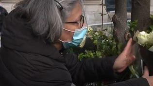 Une femme vient déposer un bouquet de fleurs en hommage à Samuel Paty, devant la Sorbonne, mercredi 21 octobre. (France 2)