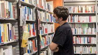 Un jeune homme masqué regarde les rayons de livres d'une librairie de Lorient en août 2020. (MAUD DUPUY / HANS LUCAS)