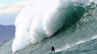 """Un surfeurs'attaque à la """"Belharra"""", une vague de10 à 15 mètres de haut, àUrrugne (Pyrénées-Atlantiques), le 7 janvier 2014. (GAIZKA IROZ / AFP)"""