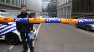 Un policier devant le siège de la police fédérale belge, à Bruxelles, où est entendu Salah Abdeslam, le 19 mars 2016. (FRANCOIS LENOIR / REUTERS)