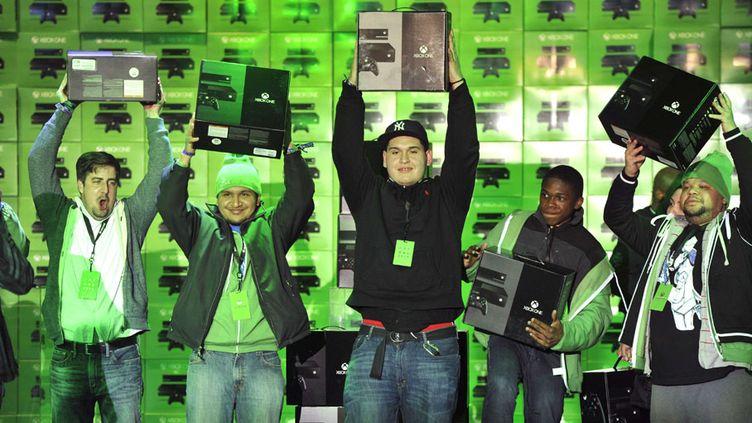 Les premiers acheteurs de la console Xbox One de Microsoft brandissent leur trophée au magasin Best Buy de Times Square à New York (Etats-Unis), le 22 novembre 2013. (CHARLES SYKES / AP / SIPA)