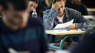 Un lycéen planche sur sa copie du bac philo, le 16 juin 2014, à Paris. (FRED DUFOUR / AFP)