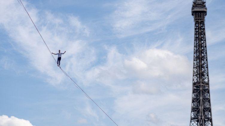 Le funambule Nathan Paulin marche sur un cable entre la Tour Eiffel et le Trocadero,à Paris, le 18 septembre 2021. (SERGE TENANI / HANS LUCAS / AFP)